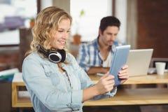 Mujer hermosa que sonríe mientras que mira la tableta en ofiise Fotos de archivo libres de regalías