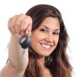 Mujer hermosa que sonríe y que lleva a cabo su llave del coche Foto de archivo