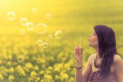 Mujer hermosa que sopla burbujas de jabón divertidas en naturaleza del verano Imagen de archivo