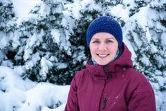 Mujer hermosa que sopla en la nieve en un bosque del pino Imagenes de archivo