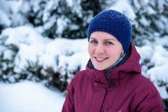 Mujer hermosa que sopla en la nieve en un bosque del pino Imagen de archivo libre de regalías