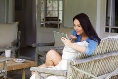 Mujer hermosa que sopla un beso a la tableta digital Imagen de archivo libre de regalías