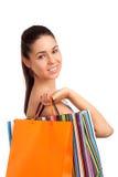 Mujer hermosa que sostiene bolsos de compras Foto de archivo