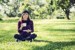 Mujer hermosa que sostiene la taza de café y que sonríe en el parque Fotos de archivo
