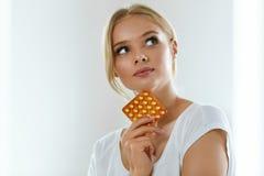 Mujer hermosa que sostiene las píldoras anticonceptivas, contraceptivo oral Foto de archivo