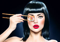 Mujer hermosa que sostiene los palillos con el rollo de sushi Foto de archivo