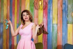 Mujer hermosa que sostiene los zapatos y las gotas elegantes en fondo de madera del colorfukl fotos de archivo libres de regalías