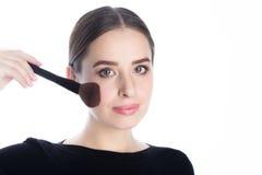 Mujer hermosa que sostiene un cepillo del polvo cerca de su cara Fotos de archivo