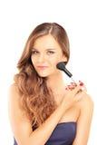 Mujer hermosa que sostiene un cepillo y que aplica maquillaje Imágenes de archivo libres de regalías