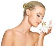 Mujer hermosa que sostiene un lirio blanco en la cara Imagen de archivo