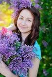 Mujer hermosa que sostiene un ramo de lilas en parque de la primavera Imagen de archivo libre de regalías