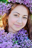 Mujer hermosa que sostiene un ramo de lilas en parque de la primavera Imagen de archivo