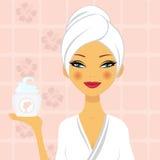 Mujer hermosa que sostiene una crema hidratante