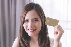 Mujer hermosa que sostiene una tarjeta de crédito de oro para el concepto financiero fotografía de archivo