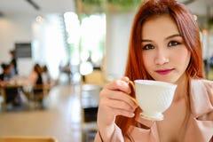 Mujer hermosa que sostiene una taza de café en su mano en cafetería del fondo de la falta de definición con el espacio de la copi Foto de archivo libre de regalías