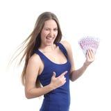 Mujer hermosa que sostiene y que señala muchos quinientos billetes de banco euro Foto de archivo