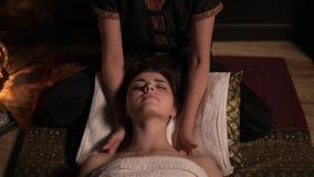 Mujer hermosa que tiene masaje tailandés de su cuello y hombros en balneario Tiro a cámara lenta del massagist femenino irreconoc