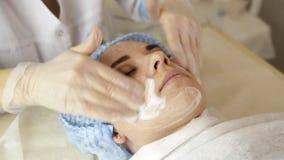 Mujer hermosa que tiene tratamiento cosmético en el salón del balneario cosmetologist en guantes médicos, cara conmovedora del `  almacen de metraje de vídeo