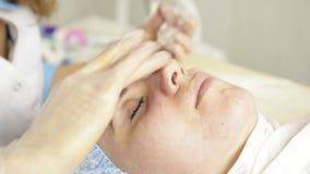 Mujer hermosa que tiene tratamiento cosmético en el salón del balneario cosmetologist en guantes médicos, cara conmovedora del `  metrajes