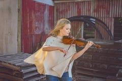 Mujer hermosa que toca el violín del vintage en depósito de chatarra imagen de archivo