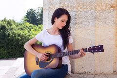Mujer hermosa que toca la guitarra acústica Fotografía de archivo libre de regalías