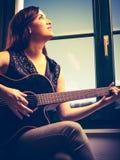 Mujer hermosa que toca la guitarra por la ventana Fotografía de archivo libre de regalías