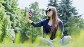 Mujer hermosa que toma el selfie en el smartphone Pasar tiempo en el parque de la ciudad metrajes