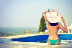 Mujer hermosa que toma el sol al borde de la piscina Fotos de archivo libres de regalías