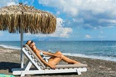 Mujer hermosa que toma el sol en un ocioso Foto de archivo libre de regalías