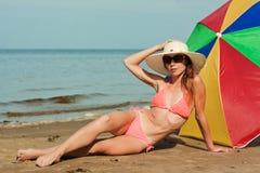 Mujer hermosa que toma el sol en una playa. Fotos de archivo libres de regalías