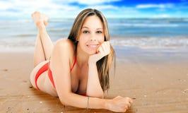 Mujer hermosa que toma el sol en una playa fotos de archivo libres de regalías