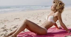Mujer hermosa que toma el sol en una playa almacen de video