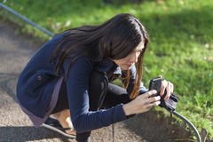 Mujer hermosa que toma imágenes con su smarphone en el parque Imagen de archivo libre de regalías
