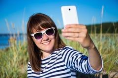 Mujer hermosa que toma la foto del selfie con el teléfono elegante en el beac Fotos de archivo libres de regalías