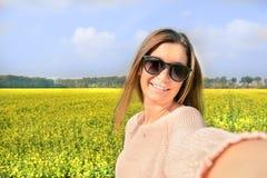 Mujer hermosa que toma la imagen del selfie de sí misma en campo amarillo con el fondo de la naturaleza Ciérrese encima del retra Foto de archivo libre de regalías