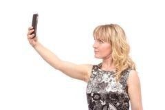 Mujer hermosa que toma la imagen del uno mismo con la cámara del smartphone Foto de archivo