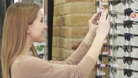 Mujer hermosa que toma las fotos de gafas de sol en la exhibición en la tienda metrajes