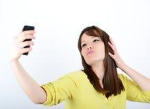 Mujer hermosa que toma selfies contra el fondo blanco Foto de archivo