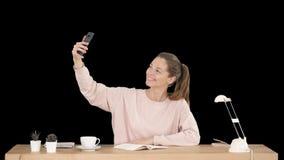 Mujer hermosa que toma un selfie con su teléfono celular que se sienta en el escritorio, Alpha Channel metrajes