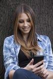 Mujer hermosa que toma una foto con su teléfono elegante Fotos de archivo libres de regalías