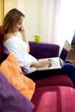 Mujer hermosa que trabaja con PC mientras que en el teléfono Fotografía de archivo libre de regalías