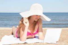 Mujer hermosa que trabaja en el ordenador portátil en la playa Fotografía de archivo