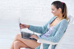 Mujer hermosa que trabaja en el ordenador portátil en sus rodillas Imagen de archivo libre de regalías