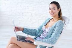 Mujer hermosa que trabaja en el ordenador portátil en sus rodillas Fotografía de archivo