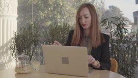 Mujer hermosa que trabaja en el ordenador portátil en restaurante almacen de metraje de vídeo