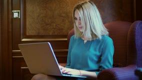 Mujer hermosa que trabaja en la pantalla del cuaderno que se sienta en la tabla en Ministerio del Interior almacen de video