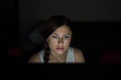Mujer hermosa que trabaja tarde en la noche en oficina Fotos de archivo
