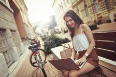 Mujer hermosa que usa el ordenador portátil al aire libre Imagenes de archivo