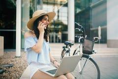 Mujer hermosa que usa el ordenador portátil al aire libre Imagen de archivo