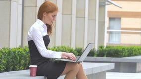 Mujer hermosa que usa el ordenador portátil con una taza de café en la terraza almacen de video